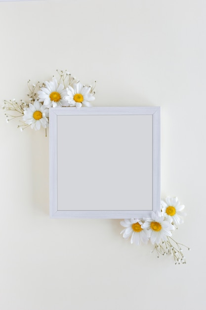 Vista superior do frame da foto em branco decorado com flores brancas da margarida sobre o pano de fundo branco Foto gratuita