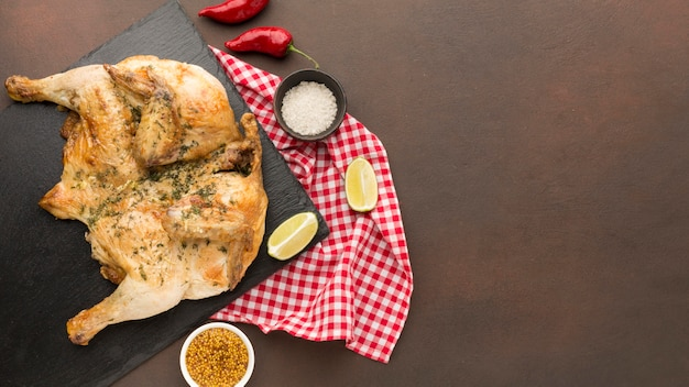 Vista superior do frango assado na tábua de cortar com condimentos e cópia-espaço Foto gratuita