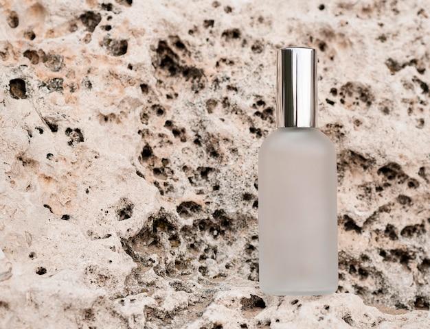 Vista superior do frasco de perfume no arranjo de pedras Foto gratuita
