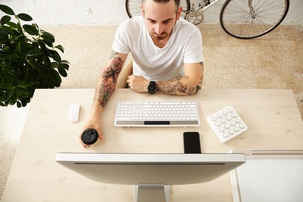Vista superior do freelancer tatuado detém o café do copo de papel para levar enquanto olha na tela do computador com controlador de música midi na área de trabalho doméstica com telefone inteligente. Foto gratuita