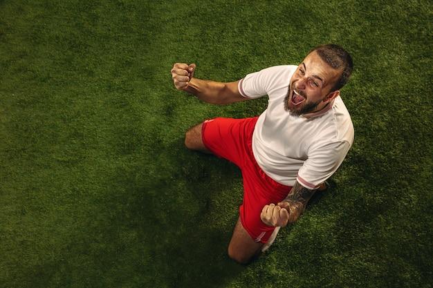 Vista superior do futebol caucasiano ou jogador de futebol sobre fundo verde de grama. jovem modelo esportivo masculino treinando, praticando. chutando bola, atacando, pegando. conceito de esporte, competição, vitória. Foto gratuita