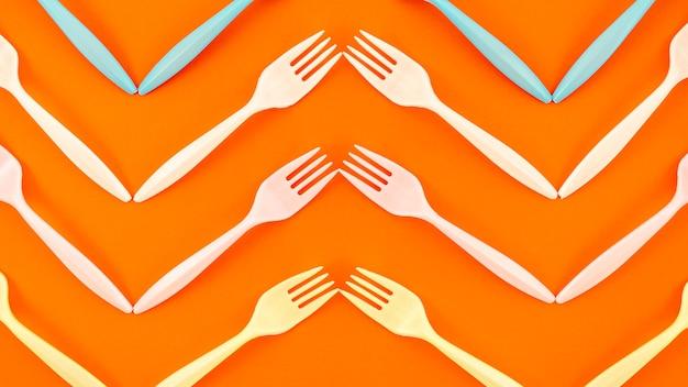 Vista superior do garfo de plástico em fundo laranja Foto gratuita