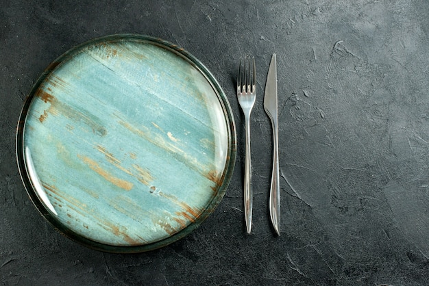 Vista superior do garfo de prato redondo de aço e faca de jantar em mesa preta grátis Foto gratuita