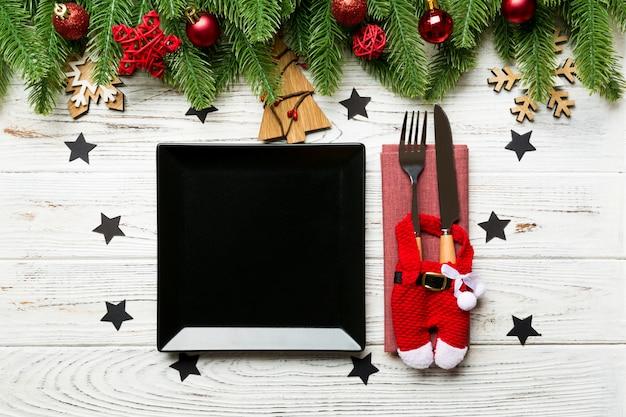 Vista superior do garfo, faca e prato cercado com abeto e decoratoins de natal em madeira. Foto Premium