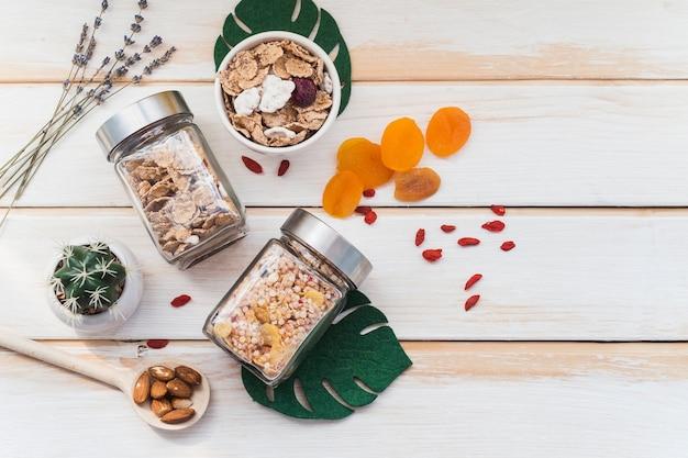 Vista superior do granola e cornflake jar perto de frutos secos e plantas suculentas em fundo de madeira Foto gratuita