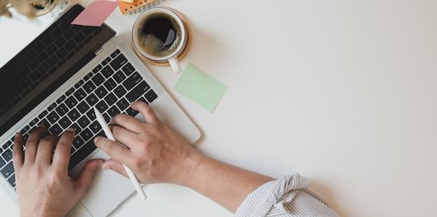 Vista superior do homem digitando no laptop no local de trabalho mínimo Foto Premium