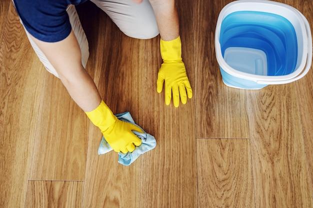 Vista superior do homem limpando o parquet em casa. ele está usando luvas de borracha nas mãos. ao lado dele está um balde com detergente. Foto Premium