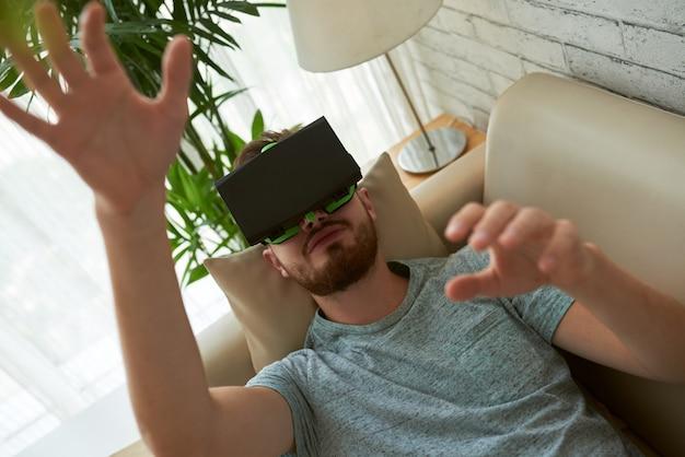 Vista superior do homem testando o aplicativo vr em seu sofá em casa Foto gratuita
