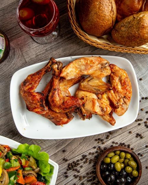 Vista superior do kebab de pernas e asas de frango, disposto em um prato com um copo de vinho na mesa de madeira Foto gratuita