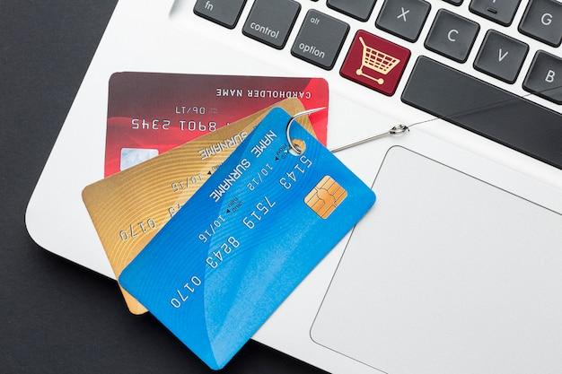Vista superior do laptop com cartão de crédito e gancho de phishing Foto gratuita
