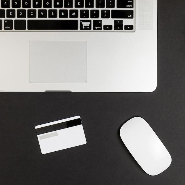 Vista superior do laptop com mouse e cartão de crédito Foto gratuita