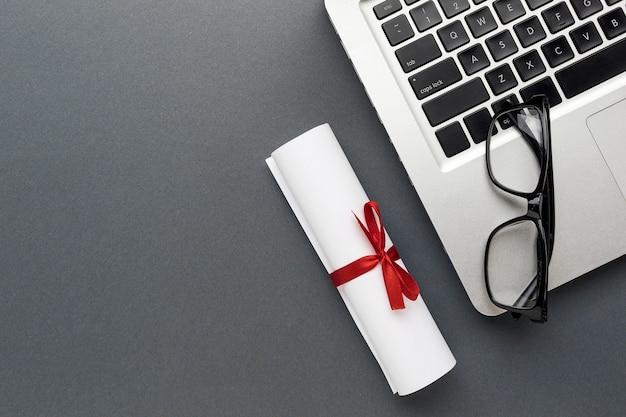 Vista superior do laptop com óculos e diploma Foto gratuita