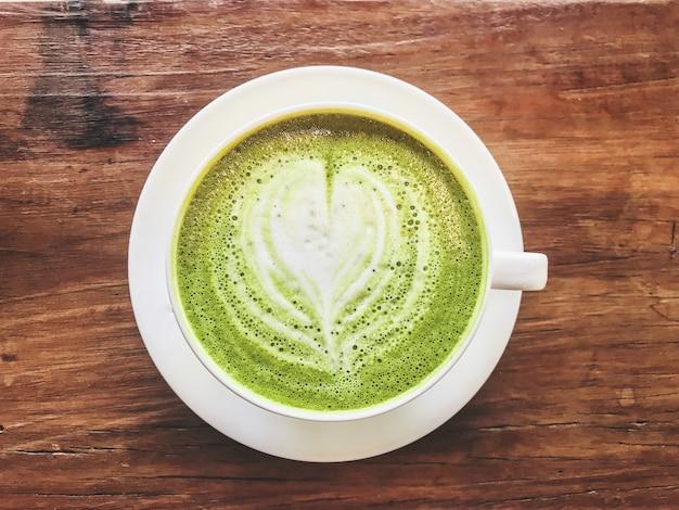 Vista superior do leite de leite de chá verde matcha quente com leite cremoso Foto Premium