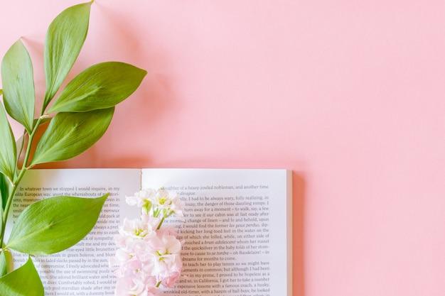 Vista superior do livro aberto e rosa matthiola incana ou mathilda lavender com galho ruscus em fundo rosa pastel com espaço de cópia. Foto Premium