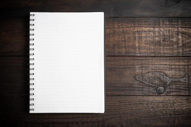 Vista superior do livro branco na madeira. Foto gratuita