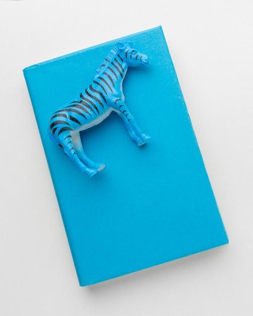 Vista superior do livro com estatueta de zebra no topo para o dia dos animais Foto gratuita