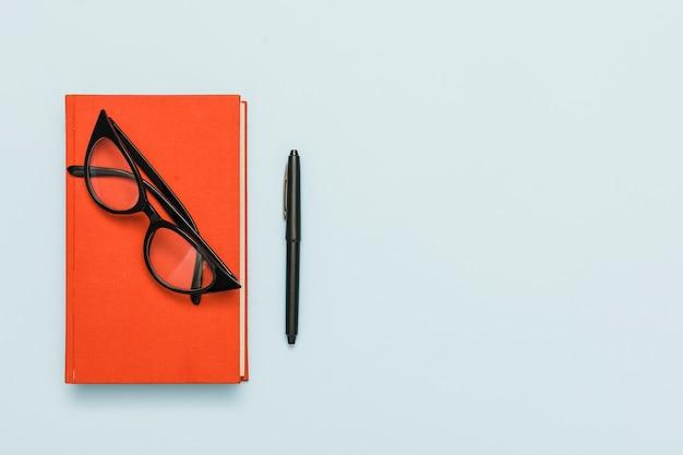 Vista superior do livro e óculos Foto gratuita