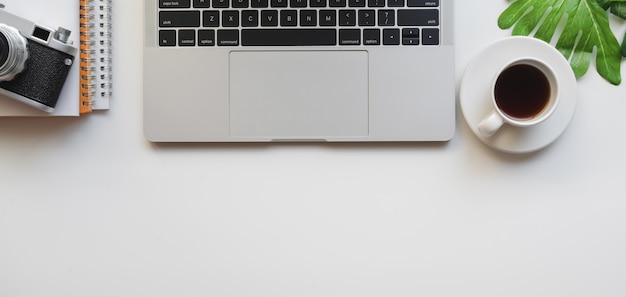 Vista superior do local de trabalho de design com computador portátil e câmera Foto Premium