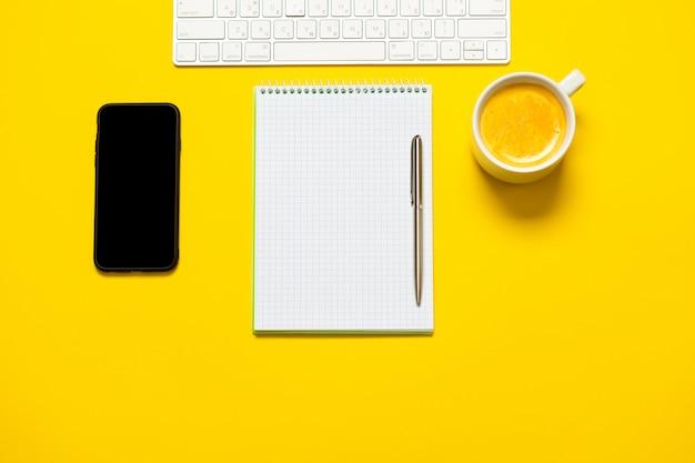 Vista superior do local de trabalho de negócios com xícara de café, espaço de trabalho vazio na mesa amarela. Foto Premium