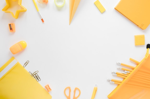 Vista superior do material escolar amarelo Foto gratuita