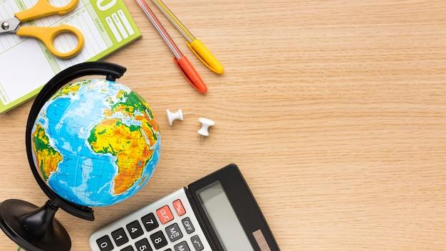Vista superior do material escolar de volta com calculadora e globo Foto gratuita