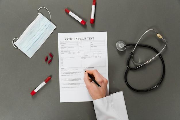 Vista superior do médico escrevendo em um teste de coronavírus Foto gratuita