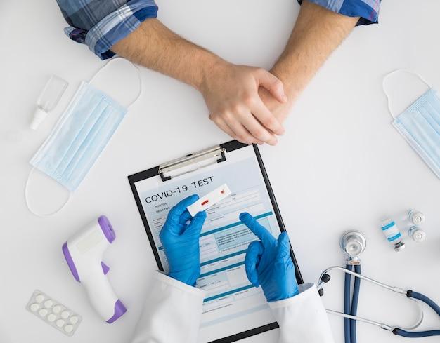 Vista superior do médico verificando teste cobiçado Foto gratuita