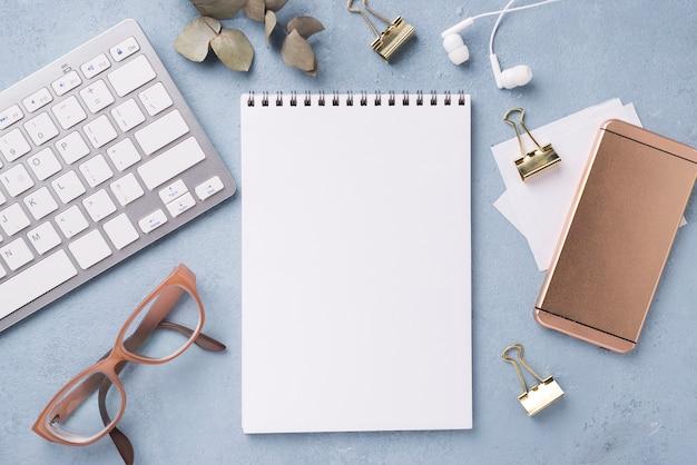 Vista superior do notebook com óculos e smartphone na mesa Foto gratuita