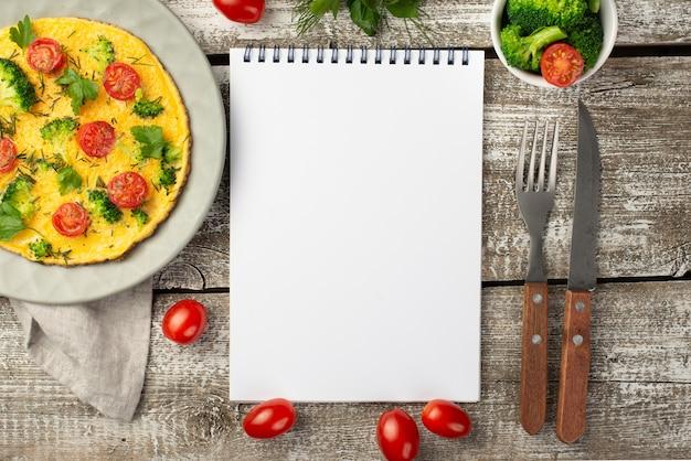 Vista superior do notebook com omelete de café da manhã e tomate Foto gratuita