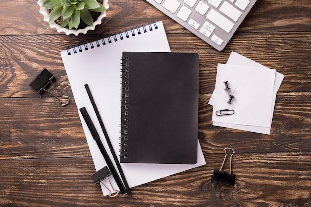 Vista superior do notebook e teclado na mesa de madeira com suculentas Foto gratuita