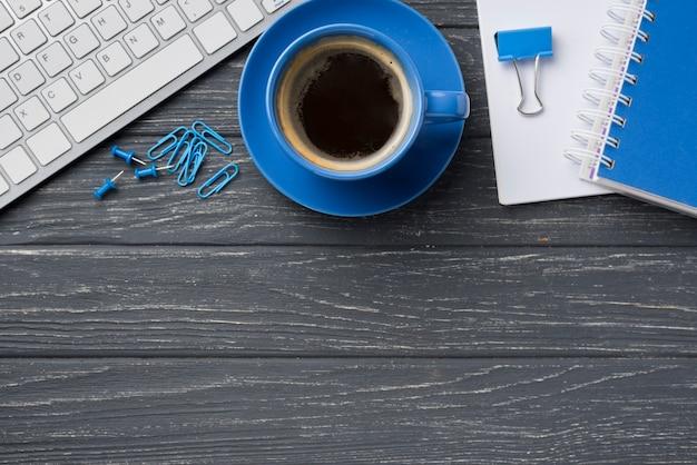 Vista superior do notebook na mesa de madeira com uma xícara de café e teclado Foto gratuita