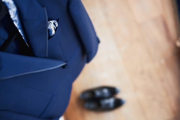 Vista superior do novo terno azul de casamento do noivo e gravata pendurado em um cabide Foto Premium