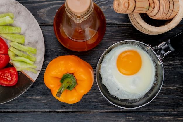 Vista superior do ovo frito em uma frigideira com pimenta orang com vinagre de maçã em um fundo de madeira Foto gratuita