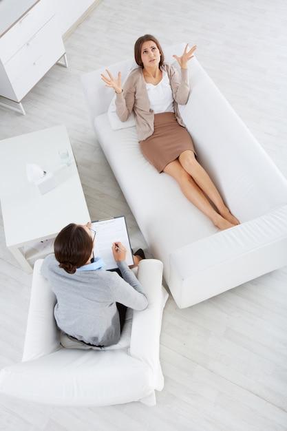 Vista superior do paciente falar com ela psicólogo Foto gratuita