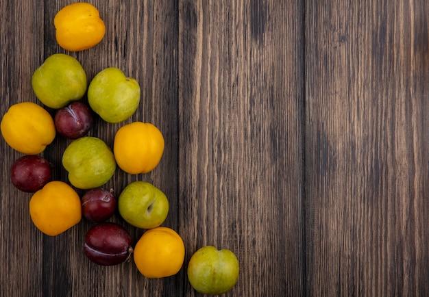 Vista superior do padrão de frutas, enquanto plumas verdes dão sabor a pluots reais e nectaculos em fundo de madeira com espaço de cópia Foto gratuita