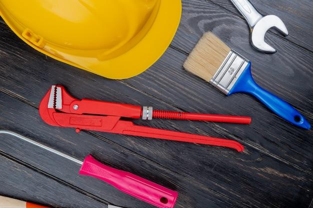 Vista superior do padrão do conjunto de ferramentas de construção como chave de fenda, chave de fenda, capacete de segurança, escova de pintura e chave de boca em fundo de madeira Foto gratuita