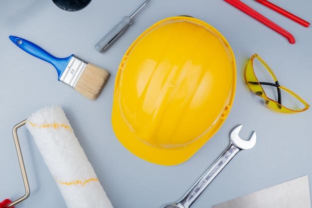 Vista superior do padrão do conjunto de ferramentas de construção como chave de fenda óculos de segurança capacete de segurança putty faca rolo de pintura pincel e chave de boca em fundo cinza Foto gratuita