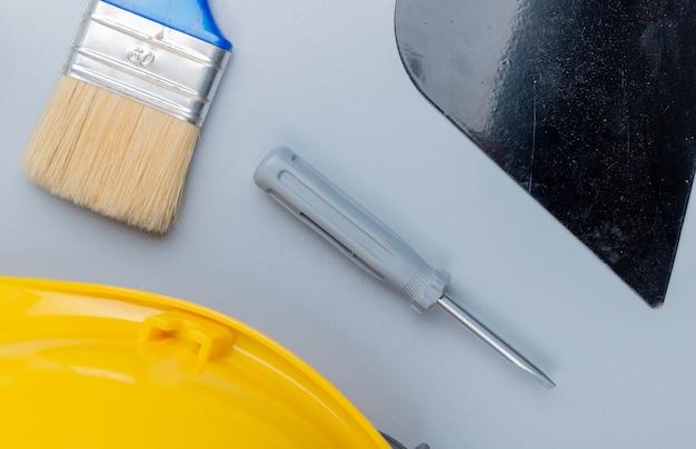 Vista superior do padrão do conjunto de ferramentas de construção como chave de fenda segurança capacete putty faca pincel sobre fundo cinza Foto gratuita