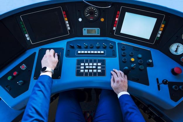 Vista superior do painel da cabine do trem e mãos do motorista do motor empurrando a alavanca e acelerando o trem de direção. Foto Premium