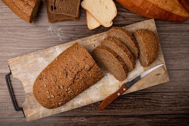 Vista superior do pão cortado e fatiado sanduíche e faca na tábua sobre fundo de madeira Foto gratuita