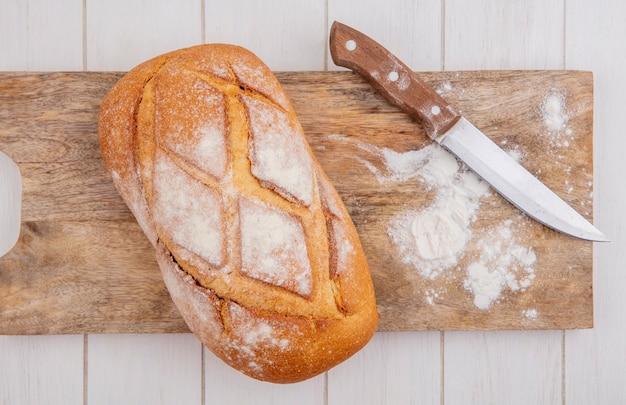 Vista superior do pão duro com faca e farinha na tábua de corte no fundo de madeira Foto gratuita