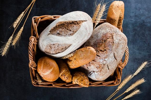 Vista superior do pão em uma cesta na mesa preta Foto gratuita