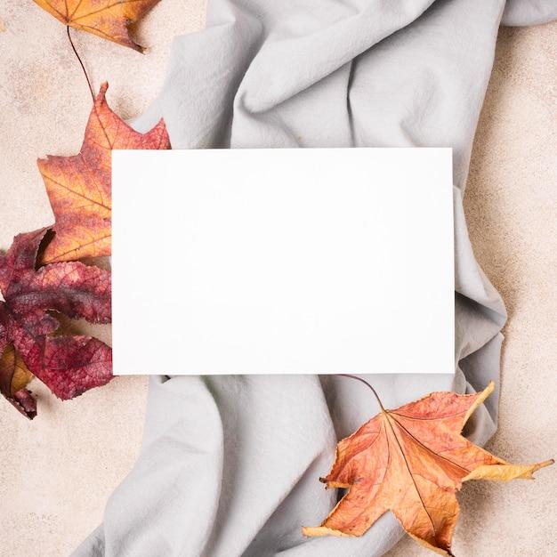 Vista superior do papel com tecido e folhas de outono Foto gratuita