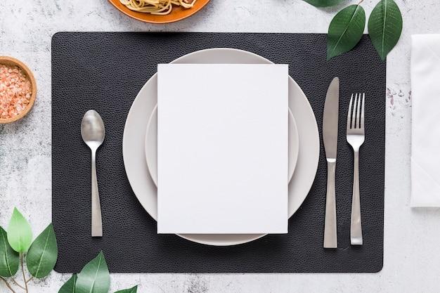 Vista superior do papel de menu em branco no prato com talheres e folhas Foto gratuita