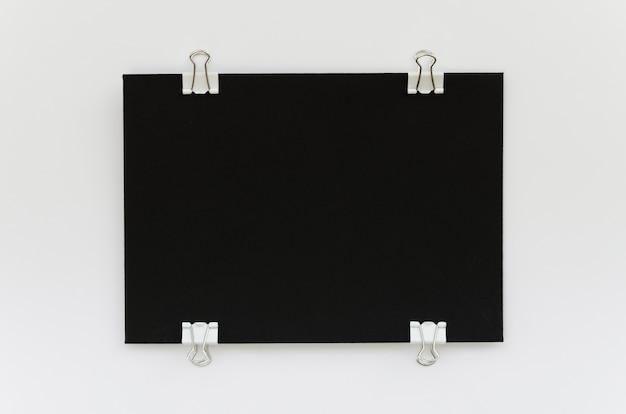 Vista superior do papel preto com clipes de metal nas laterais Foto gratuita