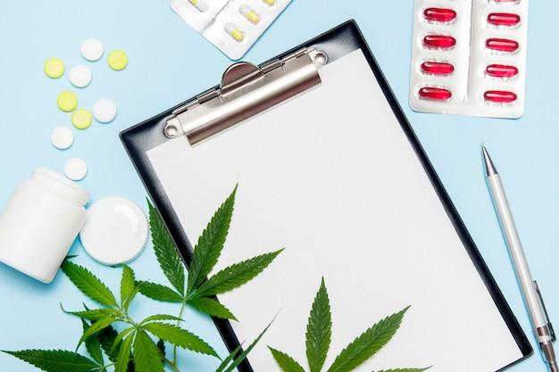 Vista superior do papel vazio para escrever a prescrição do doutor. folha da marijuana com comprimidos médicos no azul. Foto Premium