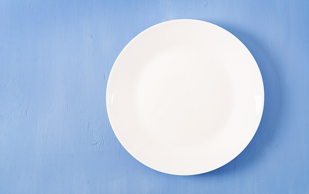 Vista superior do prato branco vazio em um fundo azul. Foto Premium