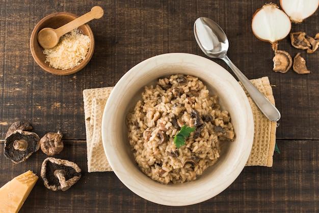 Vista superior do prato de risoto de fungos com ingredientes na mesa de madeira Foto gratuita