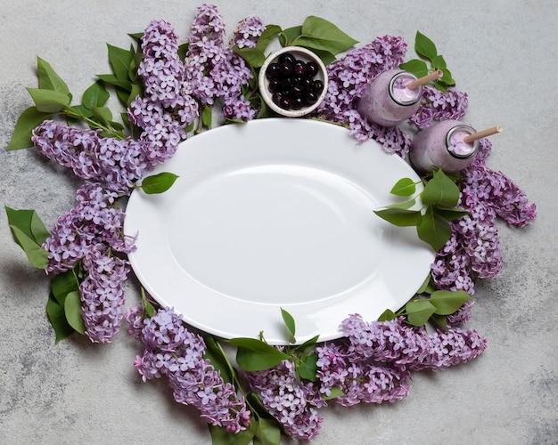 Vista superior do prato vazio sobre flores de jacinto com smoothie Foto gratuita