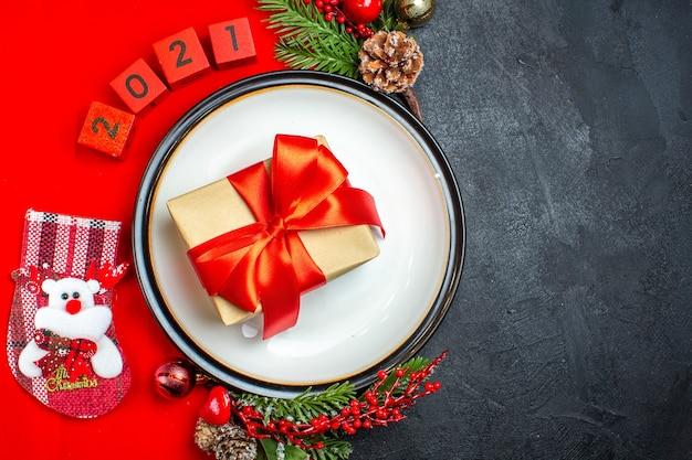 Vista superior do presente com fita no prato de jantar decoração acessórios ramos de abeto e números meia de natal em um guardanapo vermelho sobre um fundo preto Foto gratuita